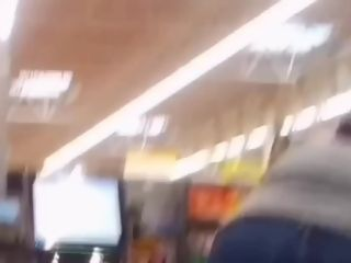 Uber-sexy booty on brunnete cougar in denim at self checkout